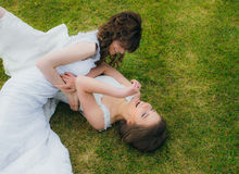 Two beautiful brides lying on the green field Royalty Free Stock Photos