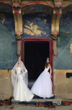 Two beautiful brides posing in old castle in autumn Stock Photos