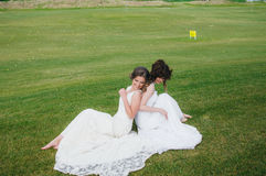Two beautiful brides sitting back to back on the green field royalty free stock photo