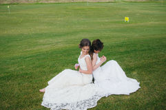 Two beautiful brides sitting back to back on the green field stock photo
