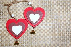 Two beautiful bright hearts on a beige background with a wicker stock photography