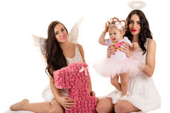 Two beautiful brunette angels with little baby Stock Image