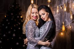 Two beautiful brunette and blonde women in silver sparkly dresses for the Christmas tree and lights. Holidays, New Year, royalty free stock photography