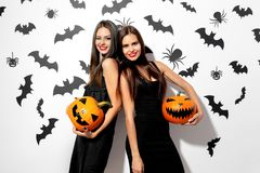 Two beautiful brunette women in black dresses have fun with jack-o-lanterns on a white background with bats and spiders.  stock image