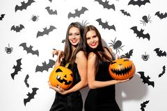 Two beautiful brunette women in black dresses have fun with jack-o-lanterns on a white background with bats and spiders.  royalty free stock photos