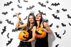 Two beautiful brunette women in black dresses have fun with jack-o-lanterns on a white background with bats and spiders.  stock photo