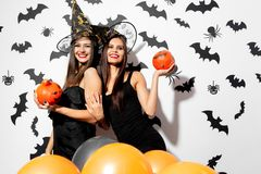 Two beautiful brunette women in witches hats have fun with Halloween pumpkins on a white background with bats and. Spiders stock photography
