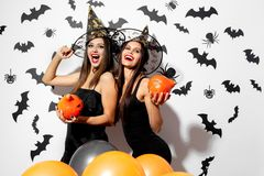 Two beautiful brunette women in witches hats have fun with Halloween pumpkins on a white background with bats and. Spiders stock image