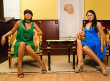 Two beautiful brunettes. Sitting on a luxury chairs in hotel lobby Royalty Free Stock Photos