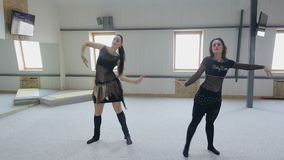 Two beautiful brunettes perform a belly dance in a dancing room. Wavelike movements with bend knees and a slow sitting down. Side steps and grace sluggish stock footage
