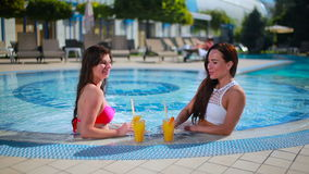 Two beautiful brunettes relaxing in the swimming pool with juice. Two beautiful brunettes in the white and pink swimsuits are sitting in the swimming pool near stock video footage