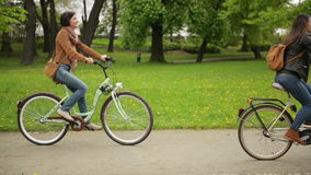 Two Beautiful Brunettes are Riding on the Bikes One After Another in the City Park in Spring. Cute Young Women in Jeans stock video
