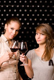 Two beautiful brunettes tasting wine. Royalty Free Stock Photography