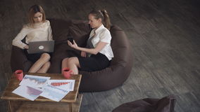 Two beautiful business woman relaxing on the couch, hands holding electronic handheld device, laptop and phone. Two beautiful business woman in skirts resting stock video footage