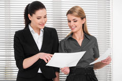 Two beautiful business woman sharing ideas with each other. Royalty Free Stock Photography