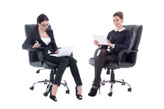 Two beautiful business women sitting on office chairs with table. T pc and laptop on white background stock photos