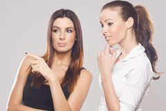 Two beautiful business women on studio background Royalty Free Stock Photo