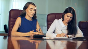 Two beautiful businesswoman office worker discussing in the office. stock footage