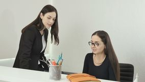 Two beautiful businesswomen discussing the deal in the office. Young woman lawyer in glasses sits at the table in the office and talks with her colleague, who`s stock footage