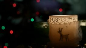 Two beautiful candles on background of flashing Christmas tree. Slider.two beautiful candles standing on the table against the background of flashing Christmas stock footage