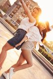 Two beautiful carefree girlfriends dancing have fun in the parking on the background of the evening sunset city, summer. Two beautiful carefree girlfriends stock photos