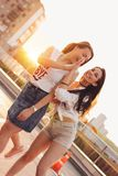 Two beautiful carefree girlfriends have fun in the parking on the background of evening sunset city, summer time. Two beautiful carefree girlfriends have fun in royalty free stock photos