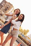 Two beautiful carefree girlfriends have fun in the parking on the background of evening sunset city, summer time. Two beautiful carefree girlfriends have fun in royalty free stock image