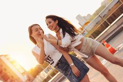 Two beautiful carefree girlfriends have fun in the parking on background of evening sunset city, summer time. Two beautiful carefree girlfriends have fun in the stock photo