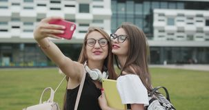 Two beautiful carefree girls taking selfie with a smart phone. Women make funny faces. Best friends taking photos. Two beautiful carefree girls taking selfie stock footage