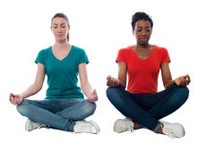 Two beautiful casual women meditating Royalty Free Stock Photo