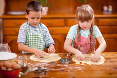 Two beautiful caucasian child making a cake, smiling happily, Royalty Free Stock Photography