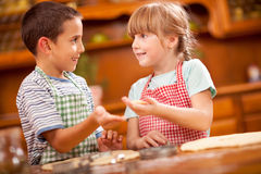Two beautiful caucasian child making a cake, smiling happily, Stock Photos
