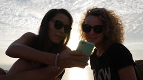 Two Beautiful Caucasian Girls Watching Funny Video on Smartphone. Lifestyle HD Slowmotion. stock video