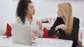 Two beautiful caucasian women discusses work at lunch break in cafe. Two businesswomen sits in cafe and discussing work issues. The colleagues talks about stock footage
