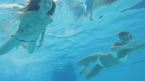 Two beautiful caucasian women in swimsuits diving and swimming underwater stock footage