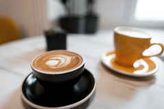 Two beautiful ceramic coffee cups stand on a table in a cafe with hot cappuccino and fragrant latte. Great morning coffee break. Close-up stock photos