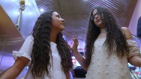 Two beautiful cheerful girls descend on the escalator during shopping in the shopping center. Two beautiful cheerful girls with long hair go down the escalator stock footage