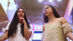 Two beautiful cheerful girls go down the escalator during shopping and discuss shopping in the mall with a good mood. HD. Two beautiful cheerful girls with long stock footage