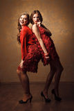 Two beautiful cheerful women in red dress Royalty Free Stock Photography
