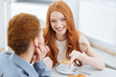 Two beautiful cheerful young women talking in cafe together Royalty Free Stock Images