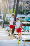 Two beautiful children, boy brothers, standing on a boat, smilin Royalty Free Stock Photos