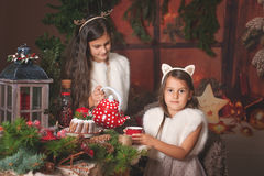 Two beautiful children, sisters, having Christmas party at family wooden cottage, cozy Christmas atmosphere. royalty free stock photos