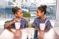Two beautiful children wearing nice family look sitting in cafeteria royalty free stock photography