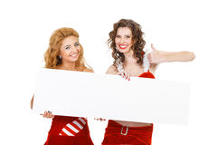Two beautiful christmas girls isolated white background holding blank poster. Stock Photos