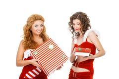 Two beautiful christmas girls isolated white background holding gifts. Stock Image