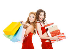 Two beautiful christmas girls isolated white background holding gifts and packages. Two beautiful christmas girls isolated white background holding gifts and royalty free stock photography