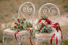 Two Beautiful colorful wedding bouquets. Beautiful wedding colorful bouquets for bride on retro chairs in forest. Beauty of colored flowers. Bridal accessories stock image