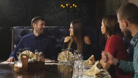 Two beautiful couples actively communicate in the restaurant and waiting for your order. A company of two couples resting at the bar and drinks , interesting stock footage