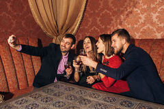 Two beautiful couples at the party take a selfie with glasses Stock Images