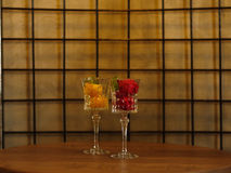 Two beautiful crystal wineglasses full of fruit ice cream. Colorful sorbet with decorative mint on a latticed background. Close-up picture of two portions of Royalty Free Stock Image
